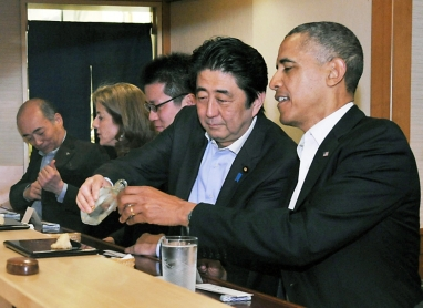 Shinzo y Obama comiendo sushi y bebiendo sake